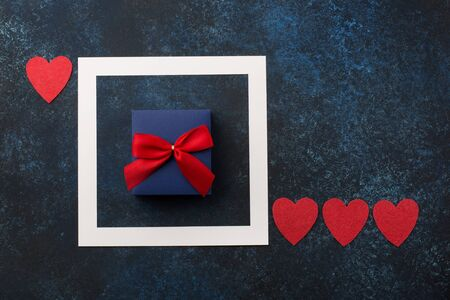 Valentines day, birthday, wedding or other holiday composition. Handmade wrapped gift box, red bow on wooden classic blue background. Copy space for text. Flat lay
