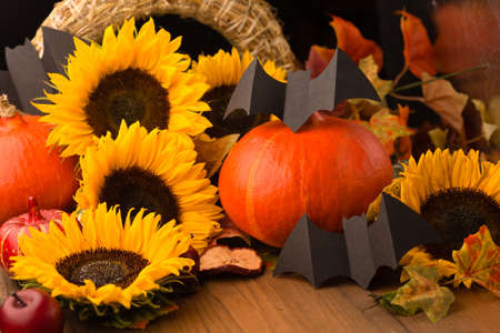 Halloween holiday composition. Sunflowers, dried leaves, pumpkins, apples and rowan berries on rustic wooden background. Autumn, fall concept.