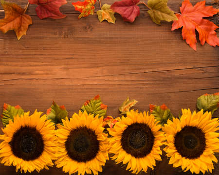 Autumn holiday composition. Sunflowers, dried leaves, pumpkins, apples and rowan berries on rustic wooden background. Autumn, fall, thanksgiving day concept. Flat lay, top view, copy space. Stockfoto