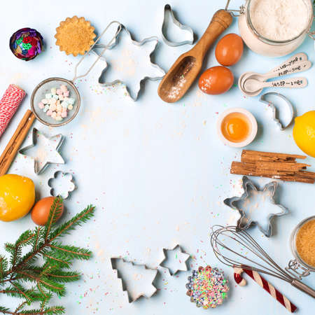 Baking ingredients for homemade Holiday Christmas pastry on blue rustic wooden background. Xmas bake sweet cake dessert concept. Top view with copy space for your greetings. DIY gift concept.