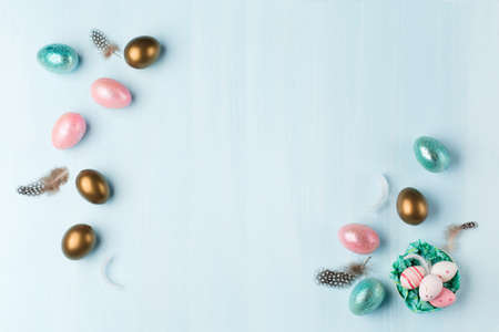 Gold, silver shiny Easter eggs on blue pastel background with space for text. Flat lay image composition, top view. Easter decoration, foil minimalist egg design, modern design template.