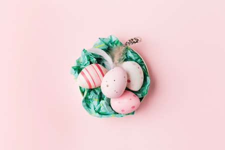 Easter eggs on pink pastel background with space for text. Flat lay image composition, top view. Easter decoration, foil minimalist egg design, modern design template.
