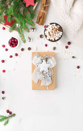 Rustic white wooden background with cup of hot chocolate drink and Christmas gift. Seasonal background from above. Flat lay, top view. Holiday card mockup, copy space