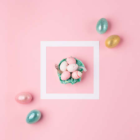 Gold, silver shiny Easter eggs on pink pastel background, white frame with space for text. Flat lay image composition, top view. Easter decoration, foil minimalist egg design, modern design template.
