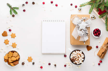 Rustic white wooden background with cup of hot chocolate drink, Christmas cookies, empty blank notepad and Xmas gift. Flat lay, top view, copy space. Zdjęcie Seryjne
