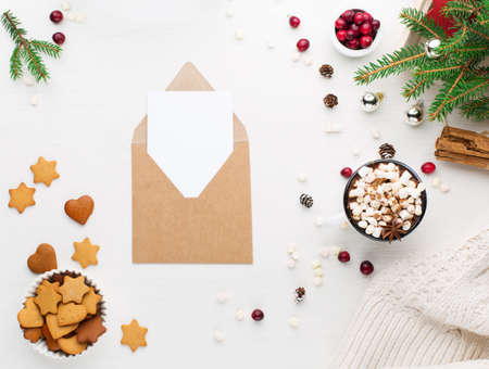 Rustic white wooden background with cup of hot chocolate drink, cookies and Christmas empty card. Seasonal Xmas background from above. Flat lay, top view. Holiday card mockup, copy space