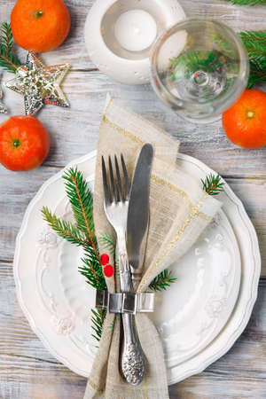Christmas or New Year Holiday Table Setting with burning candles and Xmas decorations. Top view on white wooden background. Winter holiday dinner concept. Stock fotó