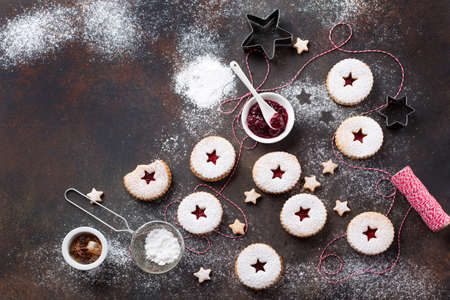 Traditional Christmas Linzer cookies with raspberry jam on dark background. Austrian biscuits filled. Top view Copy space. Holiday concept