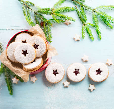 Traditional Christmas Linzer cookies with raspberry jam on blue wooden background. Austrian biscuits filled. Top view Copy space. Holiday concept. Homemade sweet present in box