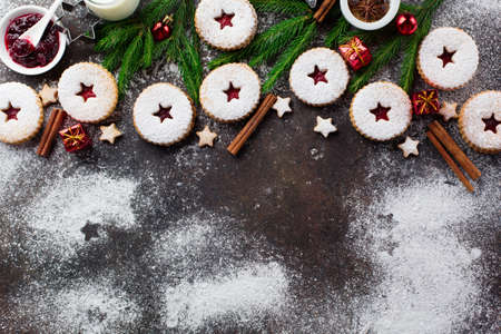Traditional Christmas Linzer cookies with raspberry jam on dark background. Austrian biscuits filled. Top view, Copy space. Winter holiday concept