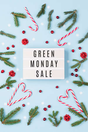 Green Monday sale text on lightbox, Christmas candy canes, fir tree branches, cranberries on pastel blue background. Online shopping sale concept. Top view, flat lay.
