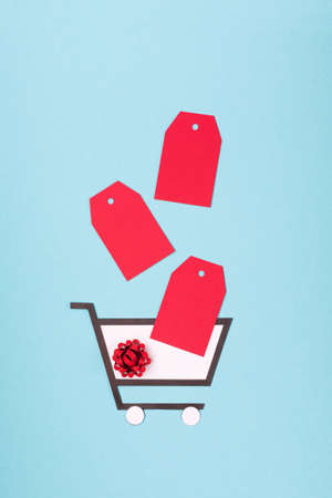 Super Sale day or Singles day concept. Shopping trolley, gift boxes and red tags on blue paper background. Online shopping of China. Top view, flat lay, copy space.