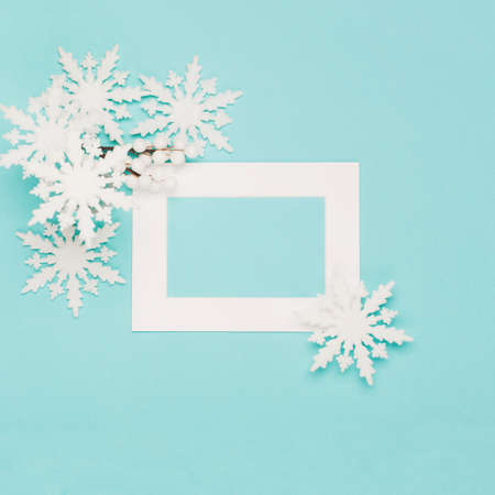 Christmas or winter composition. Frame made of snowflakes and festive decorations on pastel blue background. Christmas, winter, new year concept. Flat lay, top view, copy space