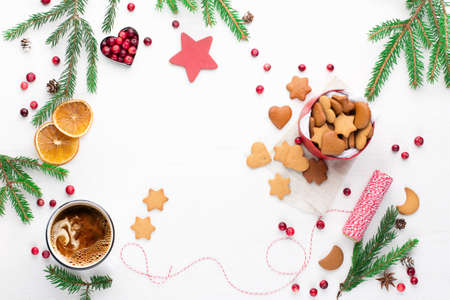 Cup of hot coffee and gift of homemade Christmas cookies on rustic white wooden background. Seasonal background from above, top view. Holiday card mockup, copy space. Winter gifts time.