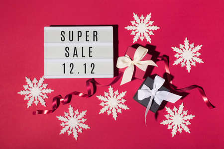 12.12 Super Sale text on white Lightbox, black and red gift boxes, white snowflakes on red paper background. Double 12 Mega sales day concept. Online shopping of China. Top view, copy space.