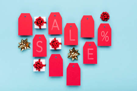 Super Sale day, Black friday or Singles day concept. Red tags, gift boxes on blue paper background. Online shopping of China. Top view, flat lay, copy space.