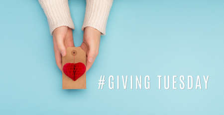 Giving Tuesday, global day of charitable giving after Black Friday shopping day. Charity, give help, donations support concept with text message red paper heart in woman hands on blue background.