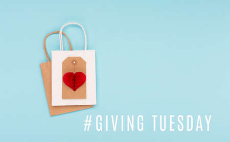 Giving Tuesday, global day of charitable giving after Black Friday shopping day. Charity, give help, donations support concept with text message, red paper heart and shopping bags on blue background.