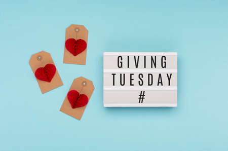 Giving Tuesday, global day of charitable giving after Black Friday shopping day. Charity, give help, donations support concept with text message on lightbox, red paper heart on blue background.