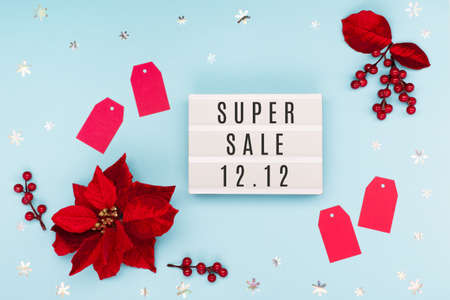 12.12 Super Sale text on white lightbox, Christmas flower poinsettia, red paper tags and snowflakes on blue background. Singles day concept. Online shopping of China. Top view, copy space.