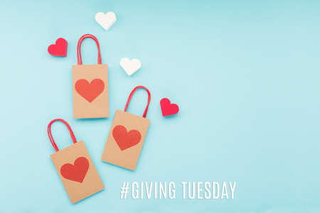 Giving Tuesday, global day of charitable giving after Black Friday shopping day. Charity, give help, donations support concept with text message, red heart and shopping bags on blue background. Stock Photo