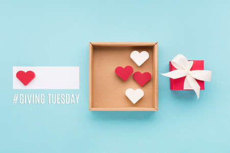 Giving Tuesday, global day of charitable giving after Black Friday shopping day. Charity, give help, donations support concept. Text message, gift box, red hearts on blue background.