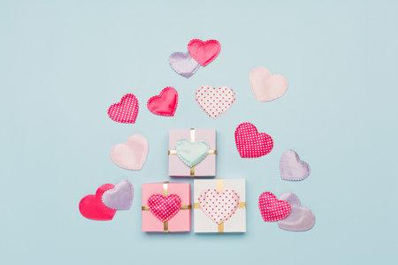 粉红色的带圆点的心形织物和蓝色背景的礼物。情人节的概念。平铺,俯视图,拷贝空间。给情人节,生日,女人,母亲节的节日贺卡。