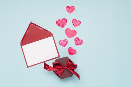桃红色纺织品心脏,空的卡片和礼物盒在蓝色背景。情人节的概念。平铺,俯视图,拷贝空间。节日节日贺卡情人节,生日,妇女或母亲节。