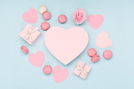 情人节卡片。粉色的彩带礼物和蓝色背景的马卡龙饼干。3月8日,女人的情人节,生日。平铺,俯视图,拷贝空间。