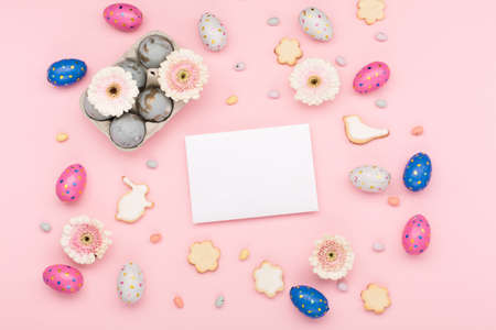 Happy Easter holiday greeting card. Homemade Easter sugar cookies, chocolate eggs, flowers on pastel pink background. Festive Easter breakfast concept. Copy space, top view.