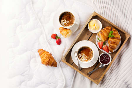 Breakfast in bed, tray with cups of coffee, fresh croissants, jam, fresh strawberries. Honeymoon, valentines day concept. Early morning at hotel. Top view, copy space. Stock Photo