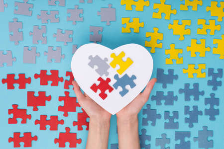 Creative concept design for April 2, Autism World Awareness day. Hands holding large white paper heart and Jigsaw colorful puzzle elements on blue background. Top view, flat lay. Stock Photo