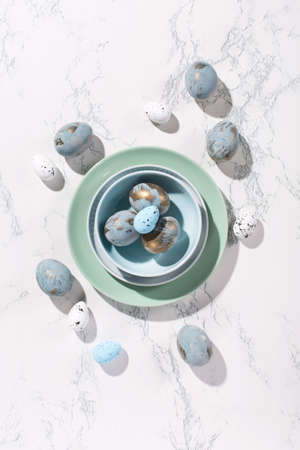 Festive Easter holiday greeting card background. Easter blue golden eggs, quail eggs and plates on gray marble table. Copy space, top view. Minimal easter card concept, hard shadows.