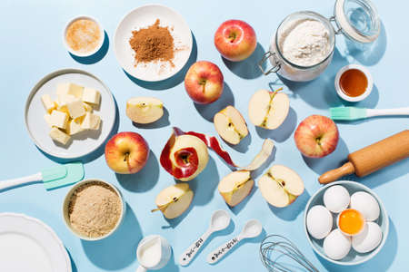 Cooking baking background with ingredients, fresh apples, spices and utensils on blue table. Baking traditional apple pie concept. Top view, copy space, hard shadows.
