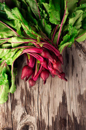 Young Fresh organic beet, beetroot on rustic wooden background. Harvest vegetable cooking concept. Healthy diet vegetarian food time. Top view, copy space.