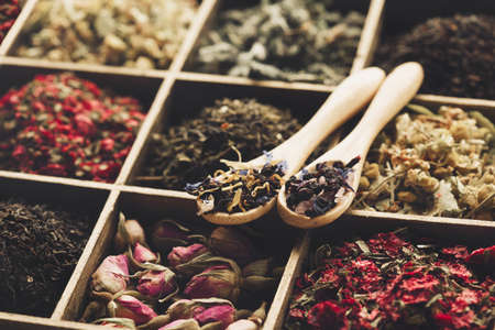 Different kind of Dry tea - green, black, mint, rose and chamomile, wooden spoons in box. Tea time concept, healthy beverage.