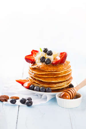 Stack of classic american homemade pancakes with fresh blueberry and maple syrup on white blue background. Selective focus, copy space. Healthy summer breakfast concept