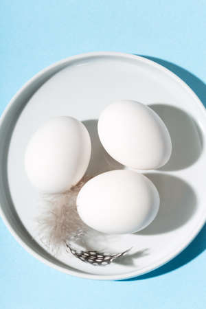 White eggs and feathers on blue table. Copy space, top view. 免版税图像