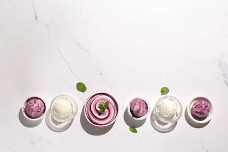 Homemade yogurt vanilla blueberry ice cream and fresh mint on natural stone marble background. Healthy low calorie summer dessert food concept. Top view, copy space. Hard sun shadows. 스톡 콘텐츠