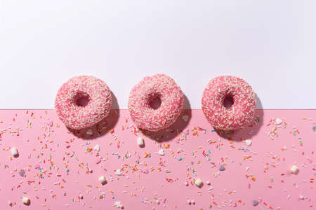 Happy National donut day concept. Donuts with pink icing and sugar sprinkle on pink background. Top view, copy space.