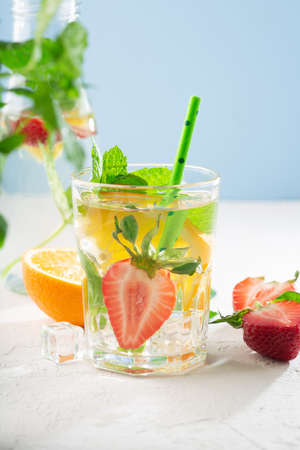 Fresh fruit lemonade drinks, refreshment infused water. Glasses with fresh strawberry, orange, lime and mint. White sun background, copy space.