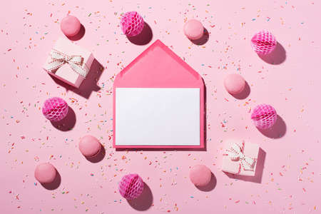 Happy birthday or party background. White empty card, sweet cakes macaroons, sprinkles, pink gift boxes and paper decorations on pink background. Top view, copy space. Festive holiday concept.