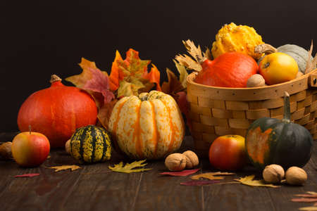 Autumn holiday composition. Dried leaves, pumpkins, apples, nuts and cinnamons on dark rustic wooden background. Autumn, fall, thanksgiving day concept. Top view, copy space.