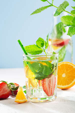 Fresh fruit lemonade drinks, refreshment infused water. Glass of water with fresh strawberry, orange, lime and mint. White sun background, copy space.