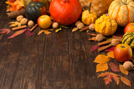 Autumn holiday composition. Dried leaves, pumpkins, apples, nuts and cinnamons on dark rustic wooden background. Autumn, fall, thanksgiving day concept, copy space.