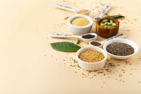 Healthy food clean eating concept. Assortment seeds, superfood on beige paper background. Set of sesame, flax seed, chia, hemp seeds, amaranth. Selective focus, copy space.