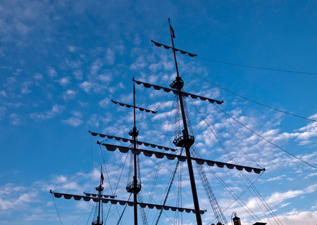 Sailing masts silhouette against blue sky