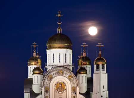 Orthodox cathedral in Magnitogorsk with golden domes and full moon behind