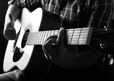 スタジオでアコースティック ギターを演奏若い男