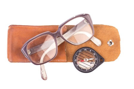 crystalline lens: old glasses and vintage compass in a leather case, isolated.